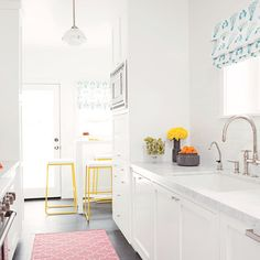 A clean white, contemporary kitchen with marble countertops, Shaker-style cabinets and modern hardware