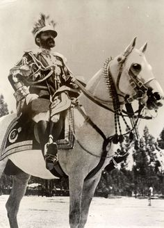 Frost House, Empire of Abyssinia (Ethiopia).  The Emperor (Negus) of Abyssinia (Ethiopia) Haile Selassie in full uniform seated on his white horse.  Location unknown, Abyssinia (Ethiopia), date unknown.