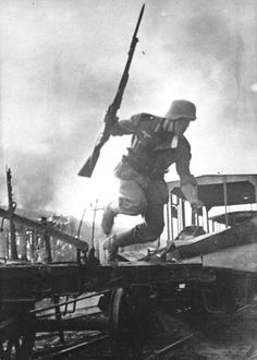 Heer soldat with affixed bayonet jumping onto a railway platform during combat.Battle of Smolensk, 1941.