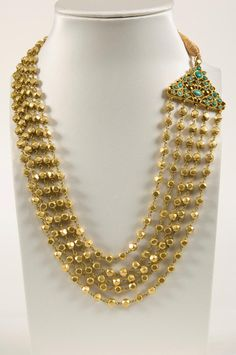 India, Gujarath, late 19th century.  Provenance: A gold necklace, Kanta Tudar, consisting of several gold strings of square beads and on both ends joined by openworked gold finials set with turqoise