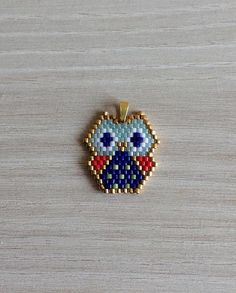 Handwoven beads pendant Form of an OWL stylized origami Very fine Japanese pearls brand Miyuki Delicas, gold plated and matching colors Size 2.2 cm X 2.4 cm Ring to put on a chain (not included) Feasible in other colors, do not hesitate to contact me