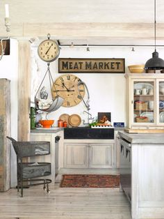 "Go Country for Less  This homeowner cut costs by whitewashing the beams, floors, and kitchen cabinets themselves. The ""Meat Market"" sign came from a restaurant where they once worked.    Read more: Antique Milk Glass Pendant Lamps Kitchen - Kitchen Designs - Country Living"