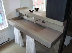Custom designed cast concrete sink with a hidden slot drain built into the wall.  The surrounding surfaces were then trowelled with a matching colored concrete to create a seamless unit for a Manhattan apartment. This apartment was featured in the New York Times (please see Press weblinks)