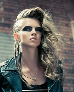 Ash blonde hair in a slightly whipped parted long hairstyle with a mix of thin braids made from the hairline and soft curls + dramatic eye makeup in strong deep shades + neon matte lips in a pale coral tone.A glamorous punk look recreated with an apocalyptic approach.Image via Tina Picard Photography.