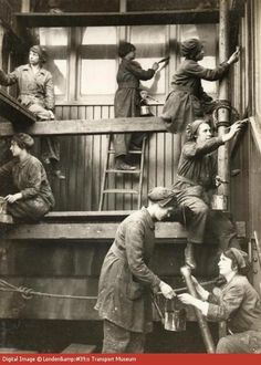 During the First World War women had to take on much of the essential work left by the men who joined the forces. This picture would have been taken to publicise the important role of women in wartime. A group of women are painting the outside of an Underground station. They are wearing trousers with long over-jackets which were supposed to 'protect their modesty' whilst allowing them enough movement to do the job. --  WWI propaganda photograph (Great Britain, UK), c. 1915 - 1918.