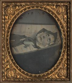 This is a post mortem in our collection. It is an elderly woman in her coffin. She was not photographed standing, strapped or wired to a posing stand. This is what an actual post mortem looks like.
