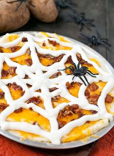 This Loaded Mashed Potato Casserole is piled high with cheese and bacon and decorated with a sour cream spider web. Perfect for #Halloween!