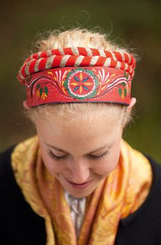 Her hair is tied up in a red ribbon and she is wearing a hårnäver. This is a kind of diadem that is used as a hair band to keep the hair high up on the fore head. A hårnäver is made from two pieces of birch-bark that are sewn together with long stitches on the back. They are decoratively painted in red or reddish-brown. Matte paint is used to cover the hårnäver and patterns are painted on free-hand. Bark is collected from the birch trees in the spring when the rising level of sap makes it easy t