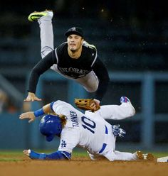Turning two -  Colorado Rockies third baseman Nolan Arenado gets airborne over Los Angeles Dodgers' Justin Turner, bottom, after forcing him out at second base and throwing to first to complete a double play on Sept. 15 in Los Angeles -  © Danny Moloshok/AP