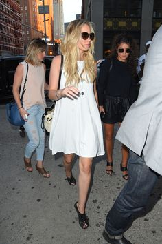 She keeps it easy and simple in a flowy white Aritzia sun dress, Pamela Love turquoise pendant necklace, oversized sunglasses, and black sandal heels.   - MarieClaire.com