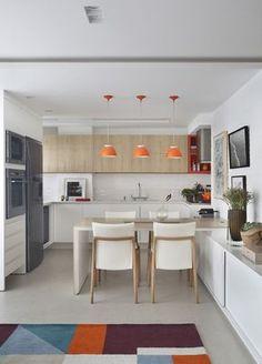 Cozinha integrada a sala. Bancada branca. Armário branco e madeira clara (parte superior). Nicho laranja. Mesa e cadeiras brancas com madeira clara. Pendentes laranja. Projeto: Patrícia Fiuza