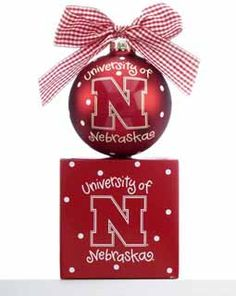 """This University of Nebraska Christmas ornament has the """"N"""" logo displayed front and center on this glass red ball.  Corn Husker fans will love to display this ornament on their tree this year.  Printed on the back is Go Huskers! and on the top is a white and red gingham bow.  Buy it now for only $21.95 at www.ornamentshop.com"""