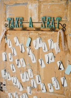 a vintage door is a great backdrop to hang escort cards with various skeleton keys as keepsakes. pretty and rustic vintage.