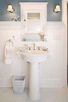 White wainscoting with a wide baseboard, twin sconces and a glass shelf over the pedestal sink.