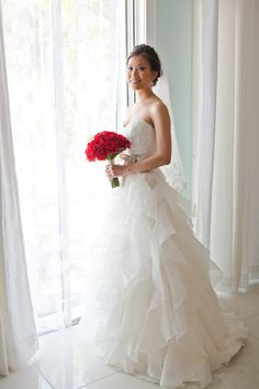 Simple yet stunning red rose bouquet contrasting strapless layered  organza wedding gown perfect for the  celestial wedding day at Key Largo Lighthouse Beach Wedding Venue in the Florida Keys