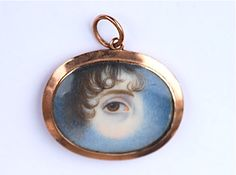 A gold pendant, circa 1820,  containing a watercolour on ivory miniature of a female eye with brown iris and brown curl. The eye is set amidst clouds, symbolic of mourning. The pendant measures 1 and 1/8 inches by 3/4 of an inch. The painting is well executed on this completely original Georgian eye miniature.    sold