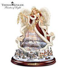 Thomas Kinkade Angel Sculpture Rotates Around Lit Village. Limited-edition Thomas Kinkade tabletop angel sculpture rotates around illuminated village. Plays Christmas carols. Mahogany-finished base. #DeckTheHalls