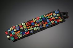 Boogie-Woogie Cuff by Julie Powell. Glass seed beads woven, one bead at a time with a needle and fishing line into a flexible fabric. Embroidered with flat beads and stones. Hand woven toggle closure. Limited edition of 30.