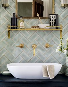 Evoke Art Deco allure in your bathroom with brass fittings against warm lustre tiles