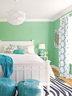 Mint green walls and teal accents make for a fresh and playful color palette.The black-blue stripes in a zebra print rug work to ground the room with a darker color, and hints of coral add warm contrast to the cool colors.