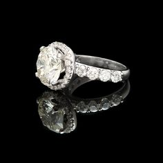 Platinum diamond ring featuring one 5.18ct round brilliant cut diamond accented by 40 round brilliant cut diamonds for 1.75cts.