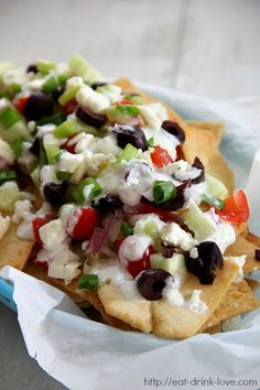 Greek Nachos - crispy pita chips topped with fresh cucumber, onions, tomatoes, kalamata olives, feta cheese, and tzatzkiki