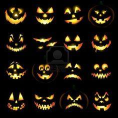 Jack o lantern pumpkin faces glowing on black background Stock Photo