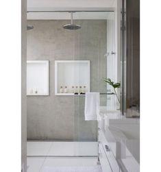 Todo cinza e branco, este banheiro conta com dois nichos dentro do box, que possui chuveiro duplo