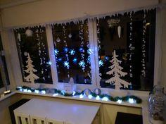 houten kerstbomen en sneeuwbolletjes als raamdecoratie