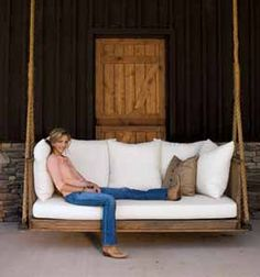 My kind of porch swing. It's pretty much a bed. Love the door behind too!