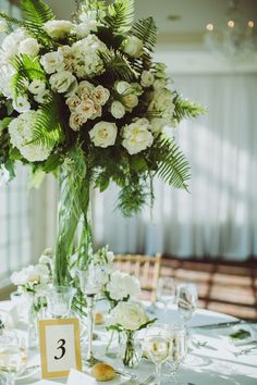 Their centerpieces resembled a garden with tons of greenery and all-white flowers. The pros at Jardiniere Fine Flowers fashioned each one with bold fern leaves, white lisianthus, white roses, white hydrangeas, white peonies and plumosa leaves. Each plant overflowed from its tall glass cylinder vase.