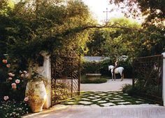 Beautiful Kelly Harmon Love the grass with flagstone, gravel break Love the iron doors and arbor large scale