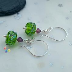 Wild Heather Earrings Sterling Silver by GlitteringprizeGlass  The lampwork beads were made with a rich green glass, decorated with a crushed glass blend left slightly raised. Teamed with sparkling Swarovski crystals & silver beads these have been added onto handmade earwires for a designer finish.  #glitteringprizeglass #giftforher #christmasgift #stockingfiller #green #heather #purple #sterlingsilver #earrings #crystal #swarovski #handmade