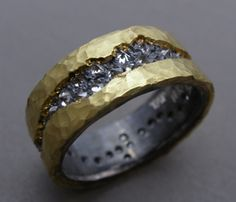 Todd Pownell: , Ring in 18k yellow gold, oxidized sterling silver, and 40 inverse set diamonds. Measures 7mm wide.