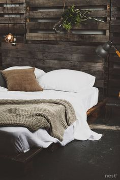 Rustic bedroom with a dark pallet bed and pallet covered walls. Black floor and white bedding with a beige bedspread.