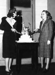 Barbara Stanwyck and her hairdresser, Hollis Barnes, were both married on the same weekend during production of Columbia's Golden Boy. Here they are photographed cutting the wedding cake that they were surprised with on set. (1939)