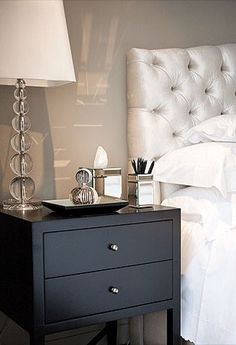 Pretty bedroom with champagne velvet tufted headboard framed by gray walls beside a two drawer black nightstand beside the bed topped with a stacked crystal sphere table lamp, small mirrored tray, mirrored tissue box holder and trinket box.