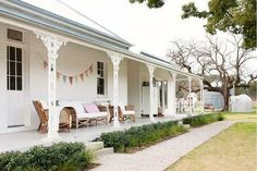 We love the splash of bunting on the whitewashed verandah! ACxx