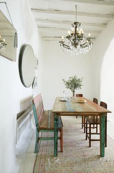Dining area - a few interesting pieces (chandelier, rustic painted furniture) can make a minimalist space pretty and charming.