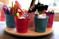 painted metal buckets for art supply storage on a lazy susan - glued to the lazy susan