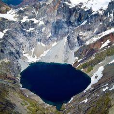 Um lago glacial remoto cercado de picos de gelo e cobertos de neve no arquipélago Tierra del Fuego, na Argentina. A topografia do Tierra del Fuego é variada, incluindo altos picos e floresta temperadas