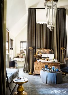 In the master bedroom, 13-foot-high bed curtains accentuate an opulent headboard—and Piper, a rescue dog. curtains in a Great Plains fabric; floor lamps, Barbara Cosgrove; antique italian lantern, Beckett Antiques; rug, designer carpets.   - Veranda.com