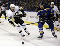 Pittsburgh Penguins' Eric Fehr, left, and St. Louis Blues' Alex Pietrangelo chase after a loose puck during the first period of an NHL hockey game, Monday, Jan. 18, 2016, in St. Louis. (AP Photo/Jeff Roberson)