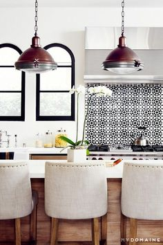 Modern kitchen with warm wood cabinets and upholstered barstools