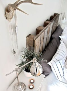 a pallet is used as a headboard, i even like the antlers in this setting :)