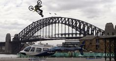 SHMCC member Travis Pastrana of the US flies over the spinning blades of a helicopter with the Sydney Harbour Bridge in the background. Motorcycle Events, Motorcycle Clubs, Travis Pastrana, Nitro Circus, Jump Over, Today Pictures, Sydney Harbour Bridge, Cool Cars, Around The Worlds