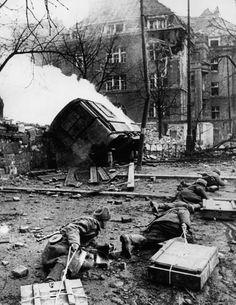 Саперы сержанта В. Мозгового ползком тащат ящики со взрывчаткой для которые подрыва дома, превращенного противником в укрепленный пункт. Из окон дома позади их прикрывают автоматчики. Улица Дер С.А. штрассе (Strasse der SA) в Бреслау.  Март 1945