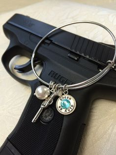 Zenja Bullet Jewelry - Silver adjustable bracelet from the 'Courtney's Colours Collection'.  Pearl, light turquoise, and a fancy little revolver!