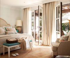 Dormitorio con cama y cabecero clásico, banqueta a los pies, butaca enfrentada y amplias ventanas con cortinas beige_429532 O