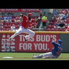 Cincinnati Reds second baseman Brandon Phillips (4) leaps for a pick-off throw as Chicago Cubs catcher Kyle Schwarber (12) slides safely into second base stealing in the top of the first inning of the MLB game between the Cincinnati Reds and the Chicago Cubs at Great American Ballpark in Cincinnati, on Wednesday, July 22, 2015. Starting pitcher Mike Leake advanced to 8-5 with the Reds 9-1 win over the Cubs in the first game of a double header. The Enquirer/Sam Greene